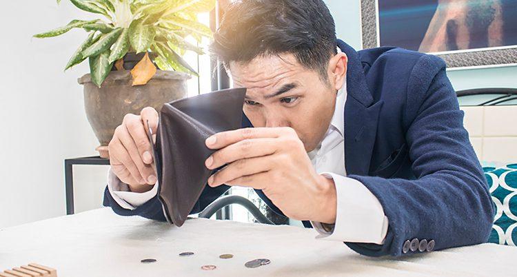 En man sitter vid ett bord. Han har vänt upp och ner på sin plånbok. Bara några mynt har ramlat ner på bordet.