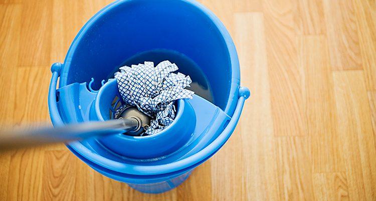 En golvmopp i en blå skurhink står på ett golv.