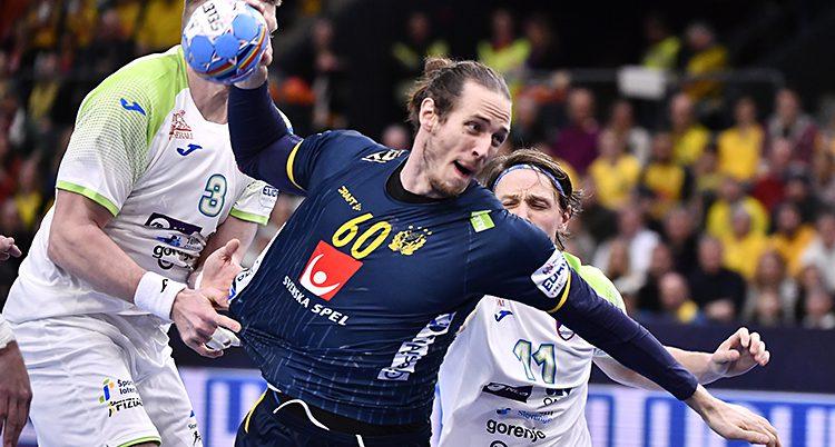 En svensk spelare hoppar för att skjuta i en match i handboll. Han har bollen i handen och mörkblå kläder på sig. Det andra laget har vita kläder.