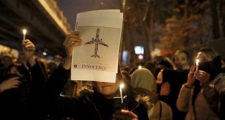 Det är kväll. Många människor står tillsammans. En del har ljus i händerna.