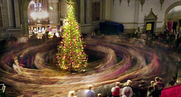 En stor julgran lyser i mitten av ett rum. Folk dansar runt granen. Bilden är tagen så att de som dansar är alldeles suddiga.