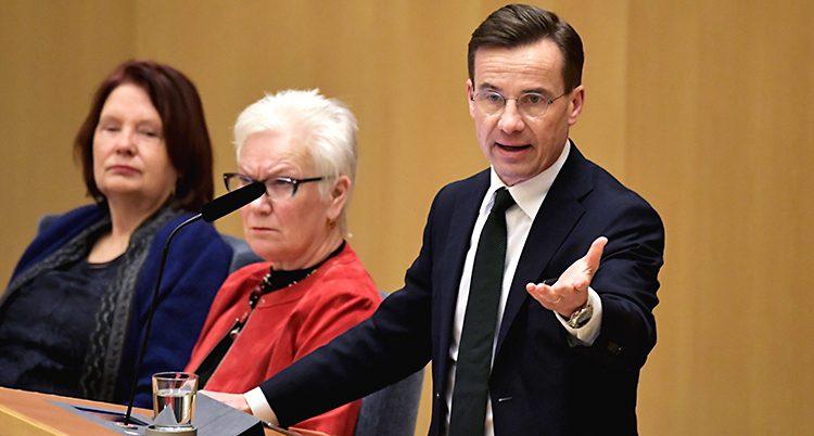 Ulf Kristersson pratar i en mikrofon. Han står i en talarstol i Sveriges riksdag. Han har glasögon och kostym.
