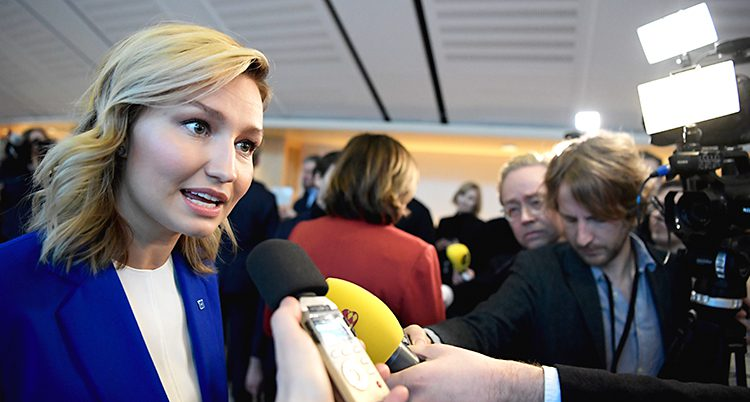 Kristdemokraternas ledare Ebba Busch blir intervjuad av flera journalister. Hon är i riksdagen. Hon pratar in i flera mikrofoner och det står folk med kameror runtomkring. Ebba Busch har blont hår och en blå kavaj.