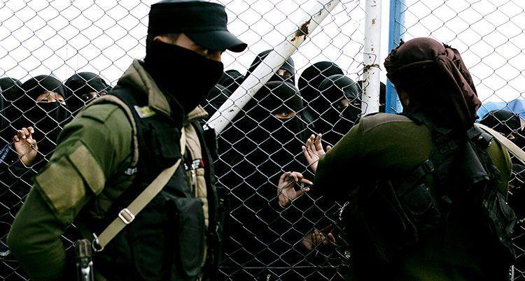 Kvinnor i svarta heltäckande abayor bakom ett högt stängsel. Framför står två män smed vapen.