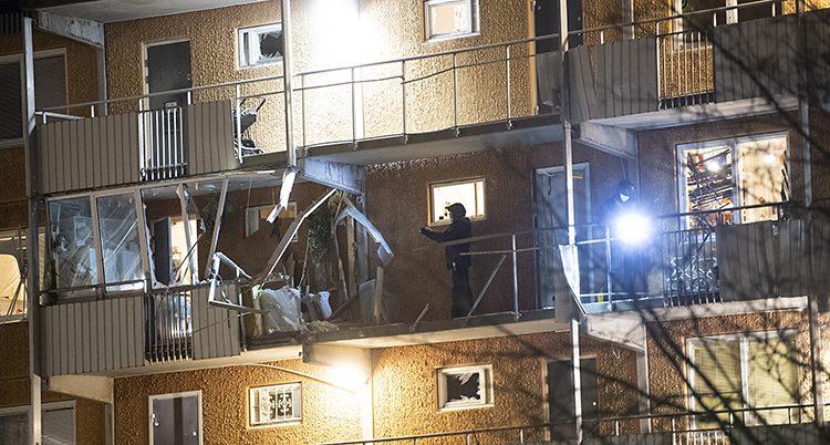 Ett hus med loftgångar på fasaden. Mitt på en av loftgångarna är hela räcket och lägenheten bakom förstörd.