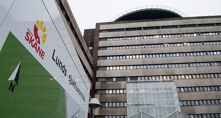 Bilden visar ett stort grått hus. Framför huset finns en skylt där det står Lunds sjukhusområde.
