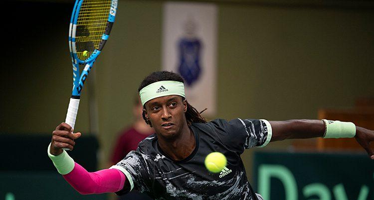 Mikael Ymer spelar en match i tennis. Han har sitt racket i luften och precis framför honom är tennisbollen.