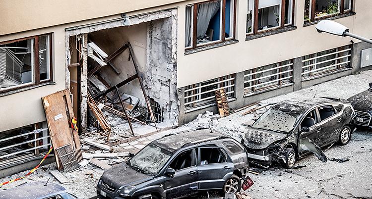 Bilden visar ett hus med lägenheter. Porten till huset är trasig efter en sprängning. Flera bilar har också blivit skadade. Och det ligger damm och grus på bilarna.