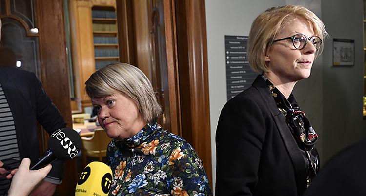 De står rygg mot rygg. Någar mikrofoner hålls fram mot Ulla Andersson.