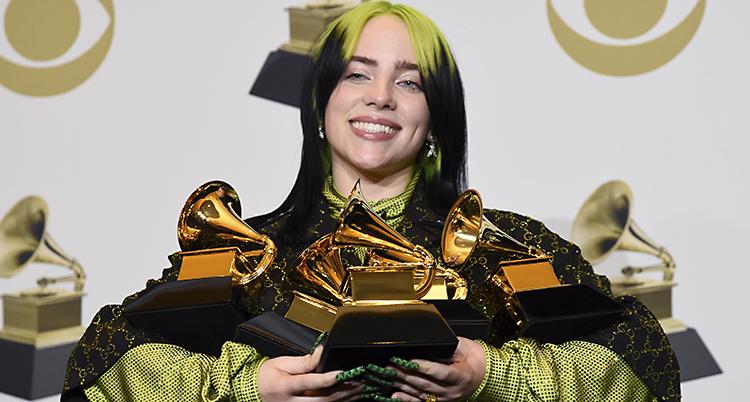 Billie Eilish ler med fyra guldfärgade priser i famnen.