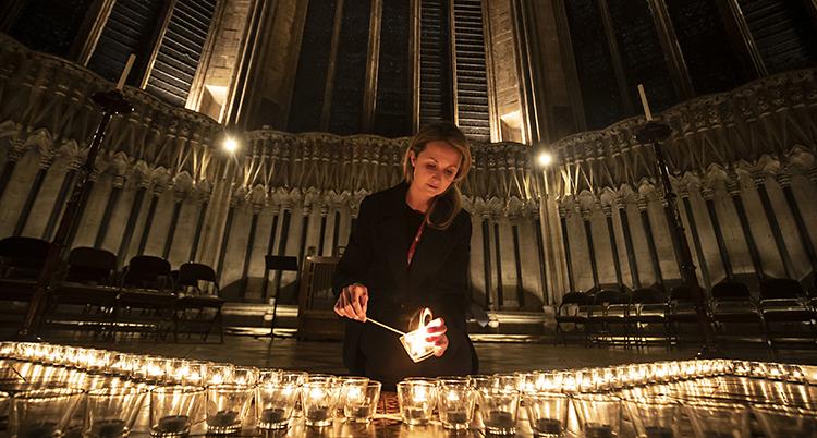 Bilden är från en kyrka i York i Storbritannien. En kvinna tänder ett ljus. Det finns en massa tända ljus runt henne.