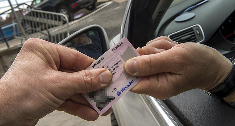 en hand lämnar över sitt körkort till en annan hand. Det sker genom ett bilfönster.