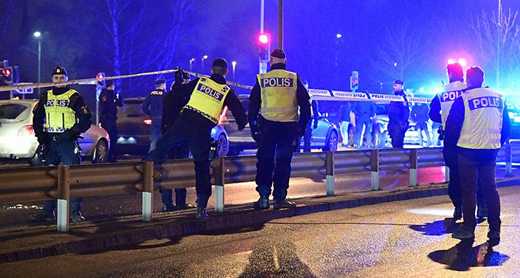 Poliser stoppar bilar vid en vägkant. Det är kväll på bilden.