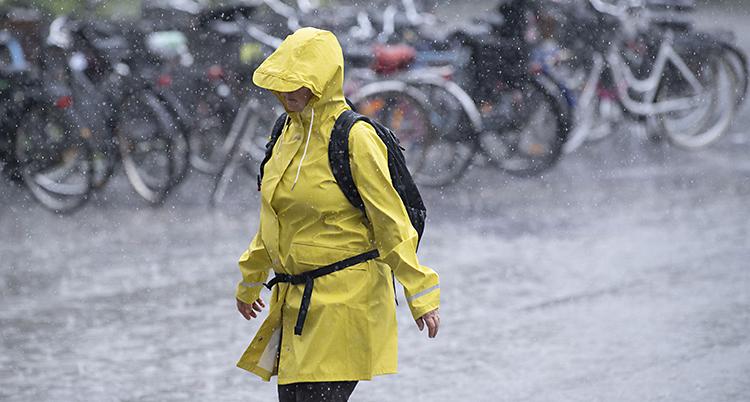 En kvinna i gul regnjacka.