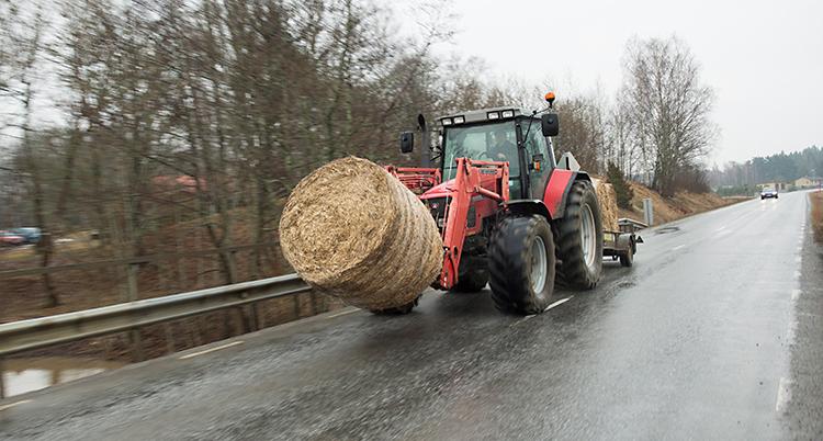 Bilden visar en bilväg. En traktor kör på vägen. Den kör hö i stora balar, ensilage.
