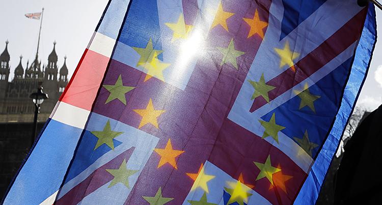 En brittisk och en EU-flagga ovanpå varandra, stjärnorna från EUs flagga lyser igenom på den brittiska tack vare en sol i bakgrunden.