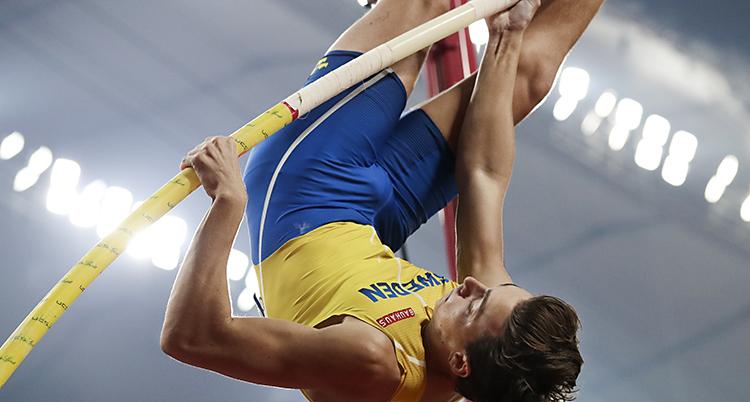 Bilden visar Armand Duplantis. Han hoppar stav. Han håller i sin stav och hänger upp och ner i luften. Han har gult linne och blå shorts.
