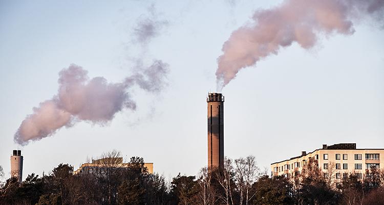 En bild på två skorstenar långt bort. Det kommer ut rök ur dem.