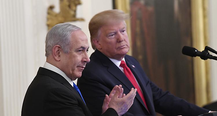 Netanyahu klappar i händer. Han står bredvid Trump som lutar sig åt Netanyahus håll.
