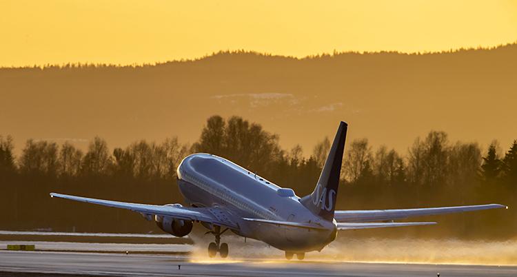 Ett flygplan lyfter från startbanan. I bakgrunden en fantastisk gul-orange himmel.