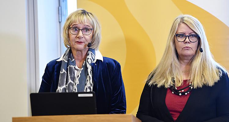 Två kvinnor står och pratar. Båda har glasögon och ljust hår.