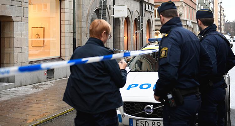 Bilden är tagen på en gata i Stockholm. Vi ser tre poliser med ryggen mot kameran. Vi ser också en polisbil och ett band från polisen som spärrar av mot ett hus. Bandet är blått och vitt.