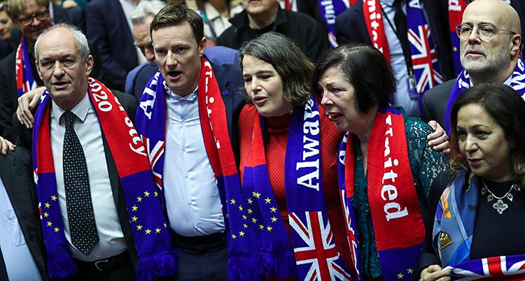 Politiker står i EUs riksdag i Bryssel. De har halsdukar på sig med Storbritanniens flagga och EUs flagga.