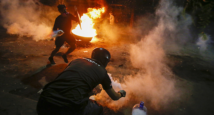 En bild tagen på kvällen. Det brinner och två män håller på at kasta rykande saker. Det kan vara granater