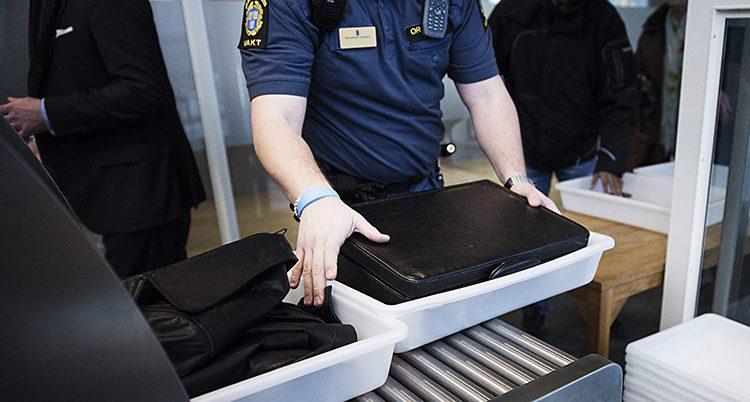 En vakt går igenom en väska i en kontroll in till en tingsrätt.