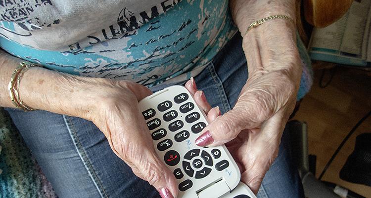 En gammal kvinna håller i en mobiltelefon.