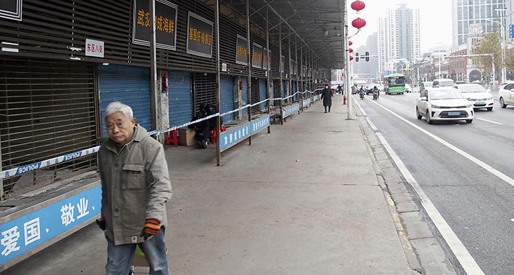 En man går förbi marknaden för fisk i Kina. Experter tror att viruset började här.