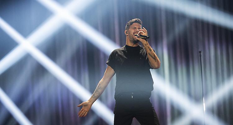 Robin Bengtsson står på scenen i Linköping. Han tar i och sjunger i en mikrofon.