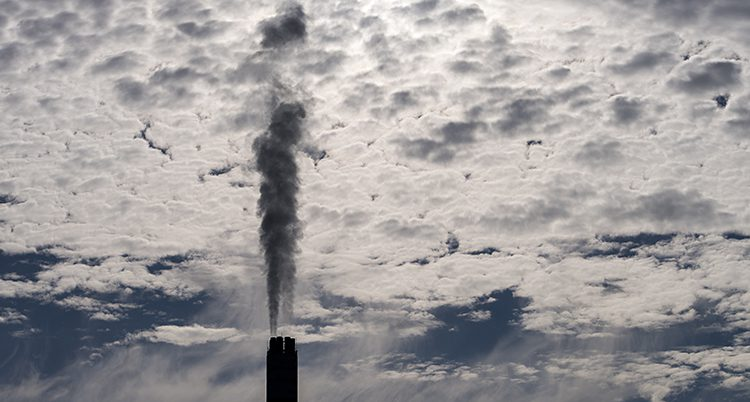 En skorsten med svart rök som bolmar upp mot en himmel med ljusa moln.