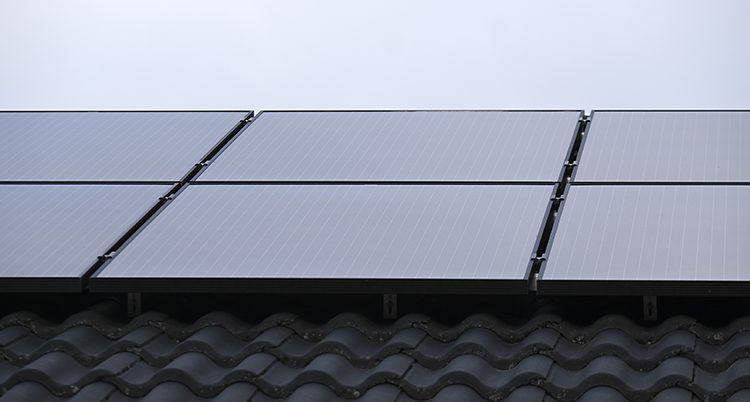 Solceller på ett tak. Det ser ut som svarta plattor.