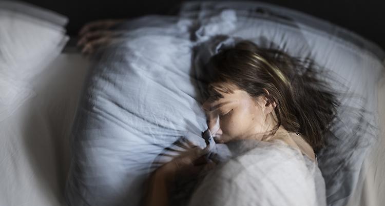 En kvinna ligger i en säng och sover.