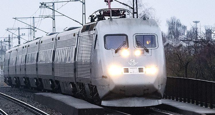 Ett tåg från SJ rullar på en räls. Det är ett grått tåg som heter X2000. Vädret är också grått.