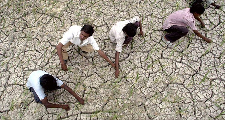 Människor sitter på torr jord i Indien
