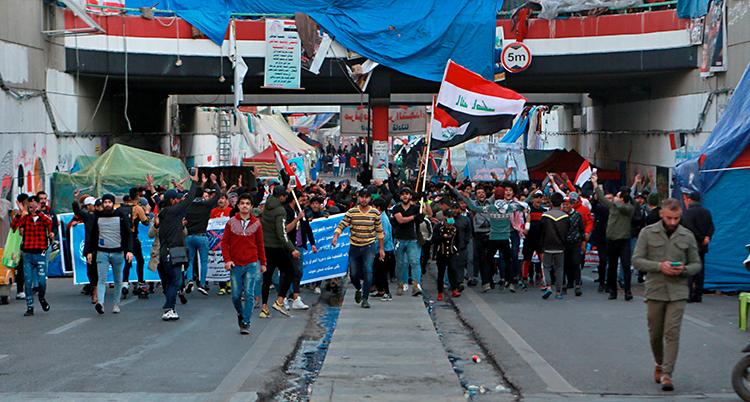 Folk går på en gata i staden Bagdad. De har plakat och flaggor.