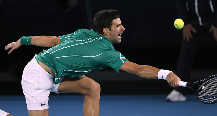 Djokovic sträcker sig efter en boll med racketen.