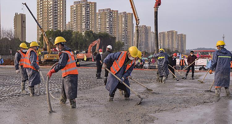 Människor står med stövlar i cement och försöker att jämna till den.