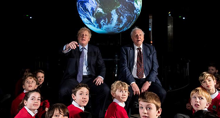 Boris, David under en lysande jordglob. Framför dem barn i röda kläder.