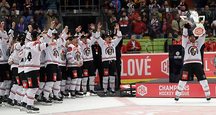 Hela laget Frölunda firar. De står på isen. Spelaren Joel Lundqvist håller upp en pokal i luften. De andra spelarna jublar och sträcker upp händerna i luften.