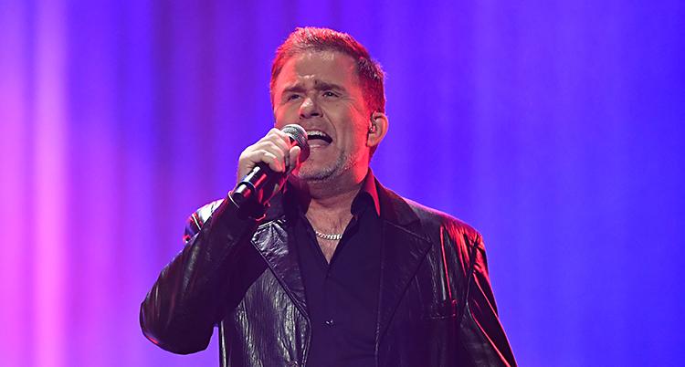 Sångaren Jan Johansen sjunger på en scen. Han håller en mikrofon i handen. Han har svarta kläder. Ljuset på scenen är lila.