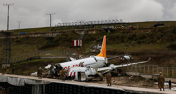 Ett flygplan ligger på marken. Det är trasigt. Några människor står runt flygplanet.