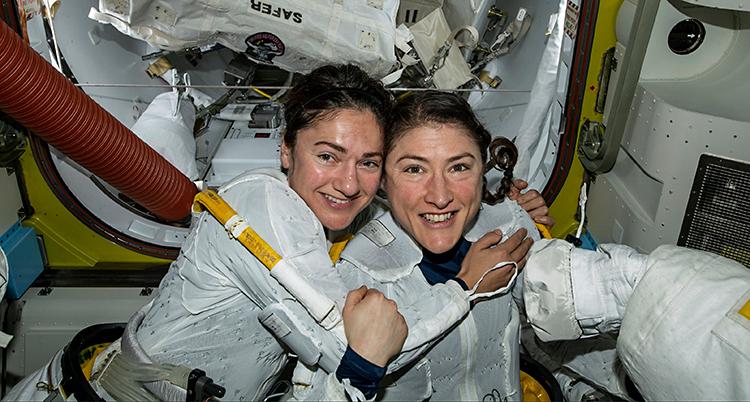 Jessica Meir och Christina Koch håller om varandra i stationen i rymden. De har vita dräkter på sig.