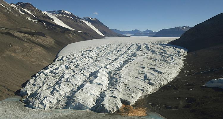 Ett område på Antarktis som är täckt av is. Solen skiner.