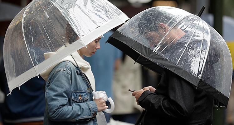 Två personer med varsitt paraply.