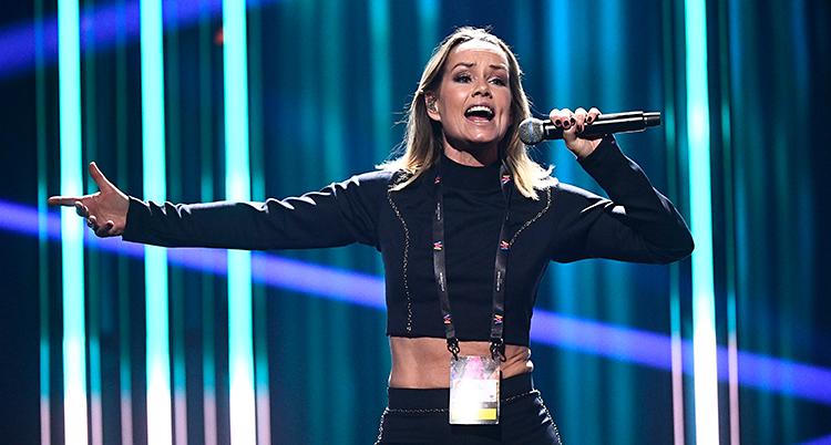 Sångerskan Linda Bengtzing står på en scen. Hon sjunger i en mikrofon. Hon har en svart tröja som visar magen. I bakgrunden syns strålar av ljus i blått och grönt.