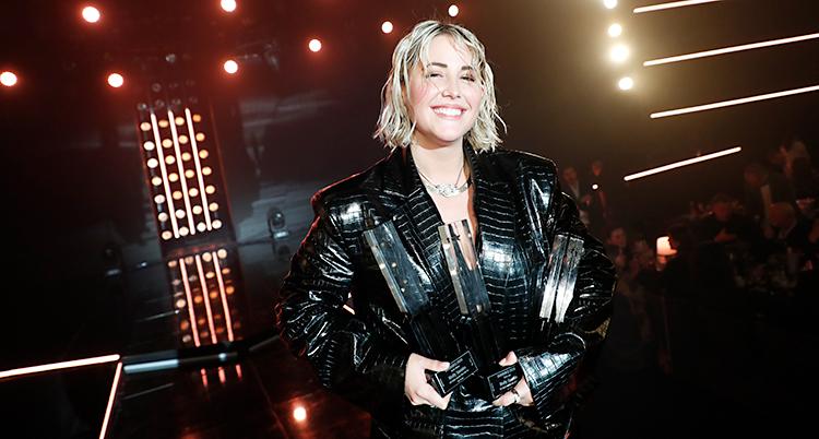 MOlly Sandén i svart stor jacka med sina priser i händerna. hon ler mot kameran.