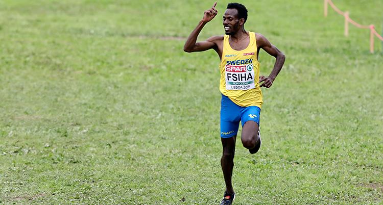 En löpare kommer springande över ett grönt fält. Han sträcker ena armen i luften och ler. Han har gult linne och blå tajts.